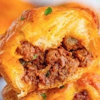 Square close up image of one Sloppy Joe Cup Recipe cut open showing filling on inside
