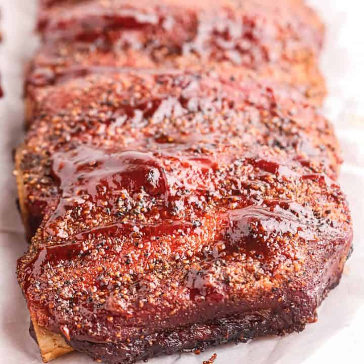 Square image of finished Smoked Beef Ribs uncut on parchment paper with BBQ Sauce