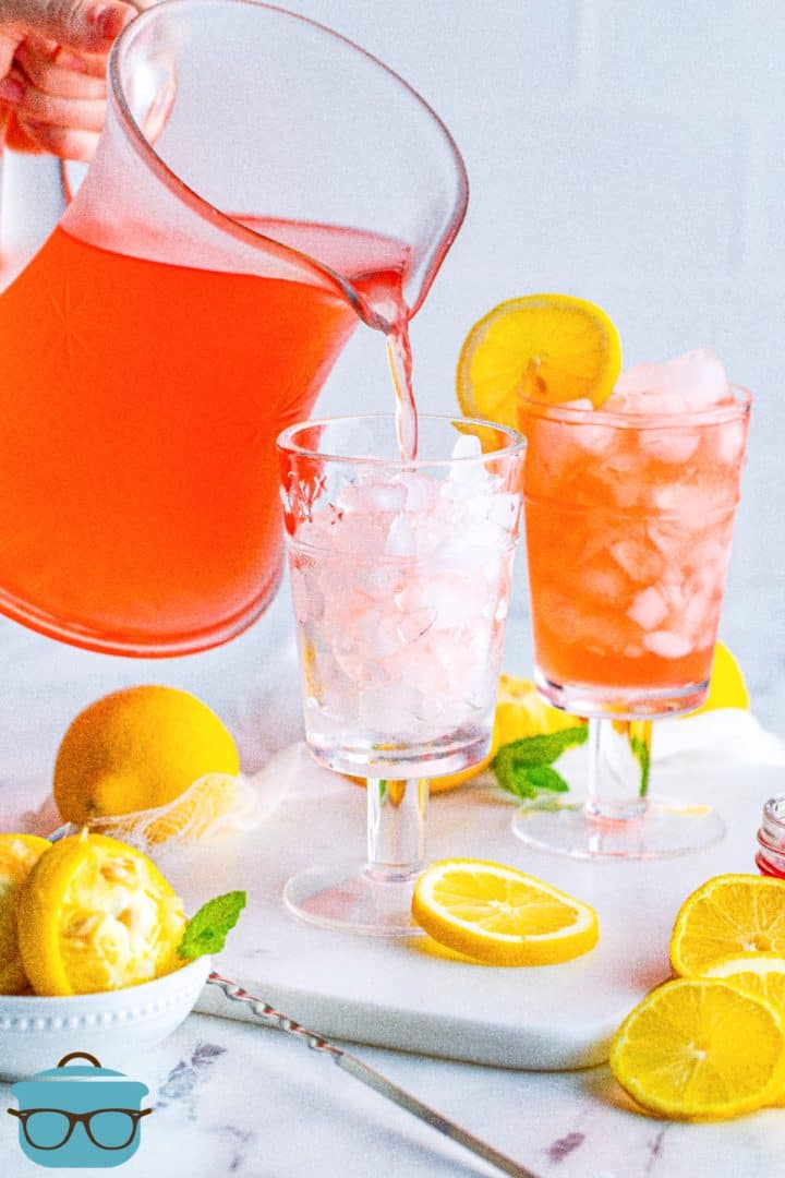 Pitcher pouring Homemade Pink Lemonade into glass with ice