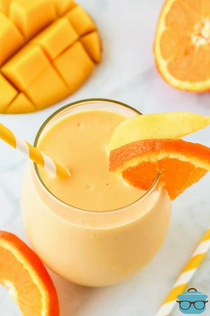 Overhead photo of a Mango Smoothie with a straw and orange and mango slice.