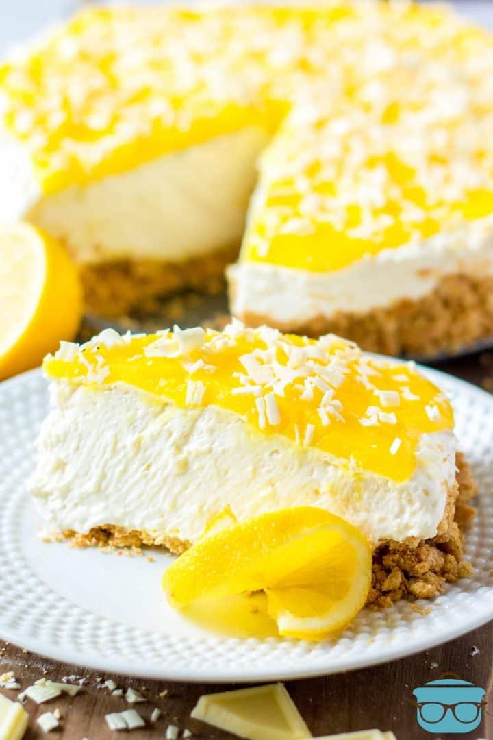 Slice of No-Bake Lemon White Chocolate Cheesecake on white plate with slice of lemon