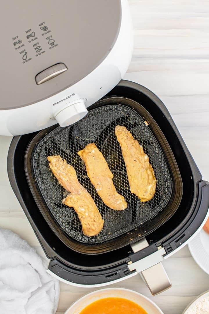 Chicken tenders being flipped in air fryer basket