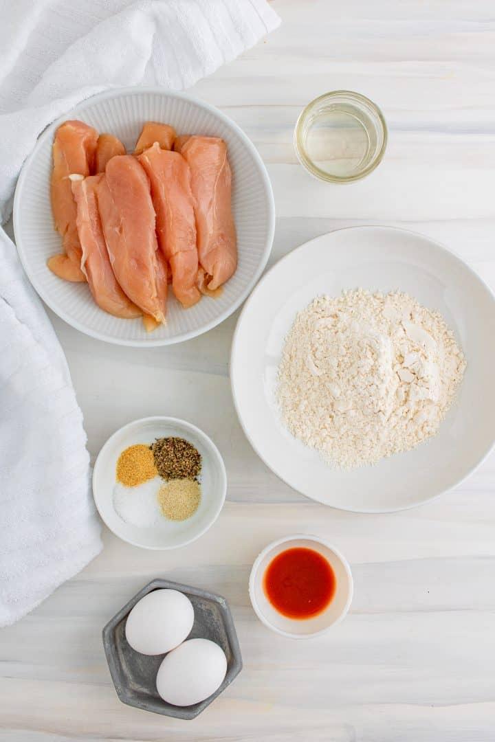 Ingredients needed: flour, salt, pepper, garlic powder, onion powder, eggs, water, hot sauce, chicken tenders, olive oil spray