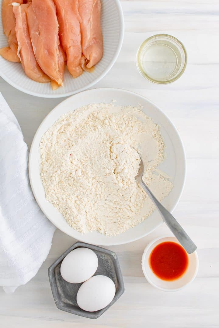 Flour mixture being stirred up in white bowl