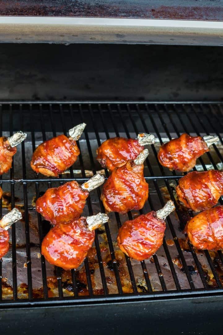 BBQ sauce brushed on chicken drumsticks on smoker