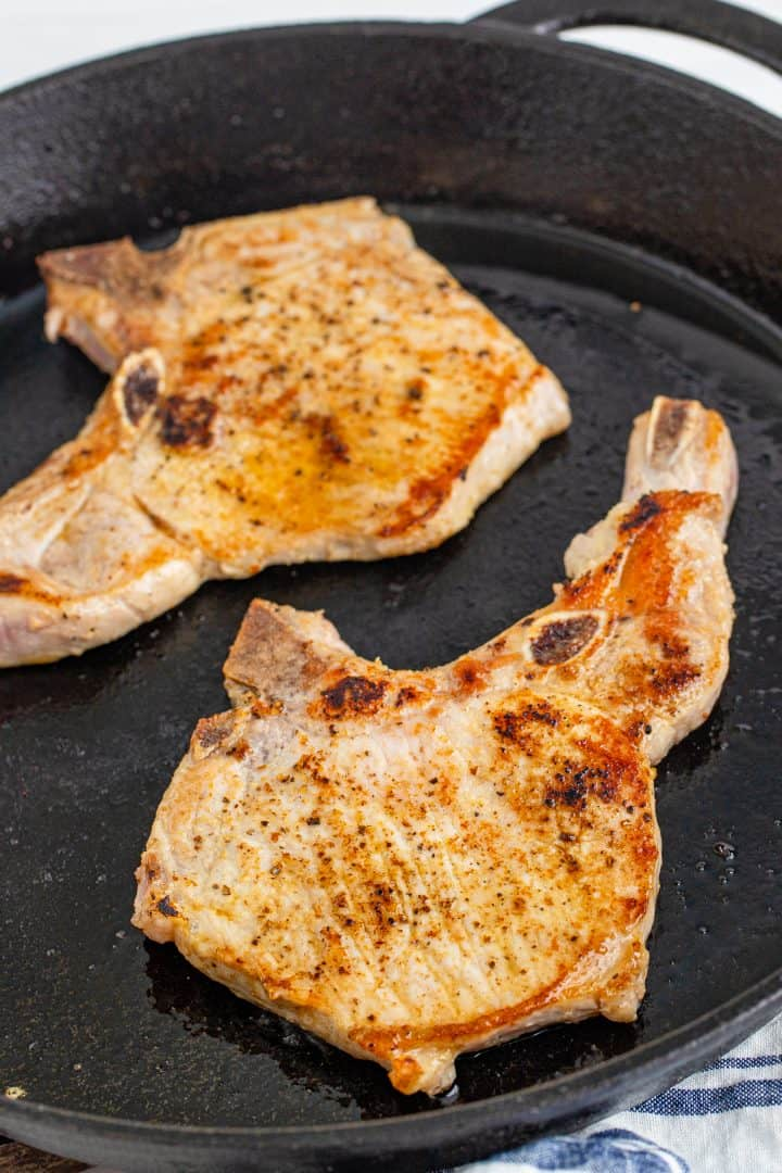 browning two pork chops in a cast iron skillet