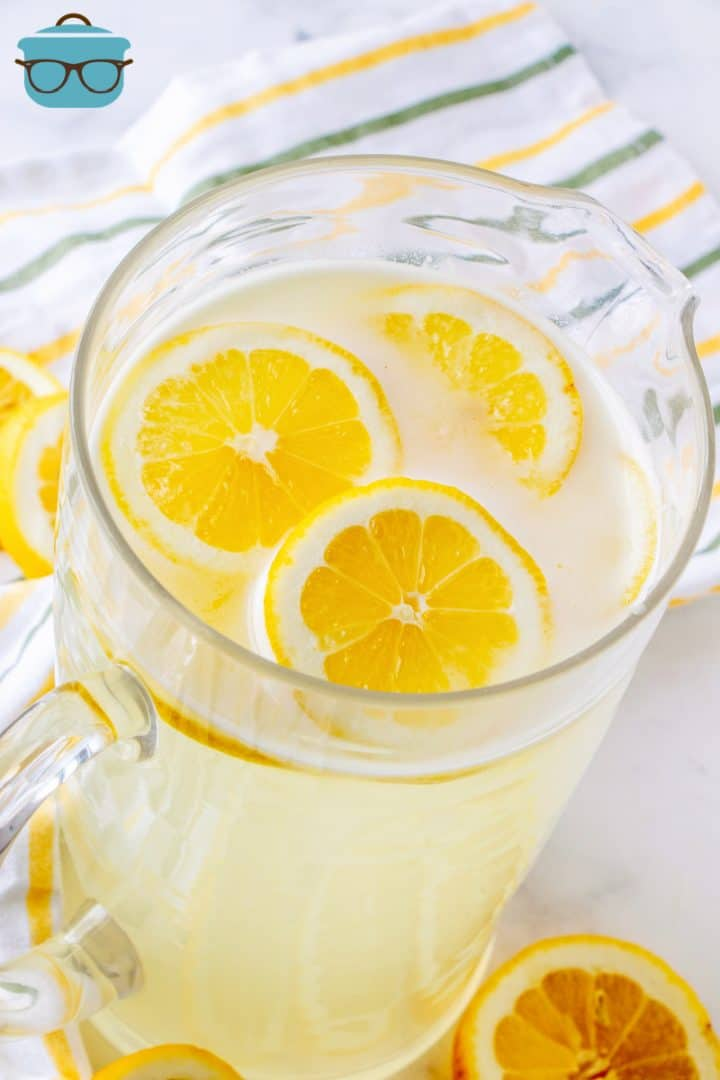 fresh squeezed lemonade shown in a large glass pitcher with sliced lemons