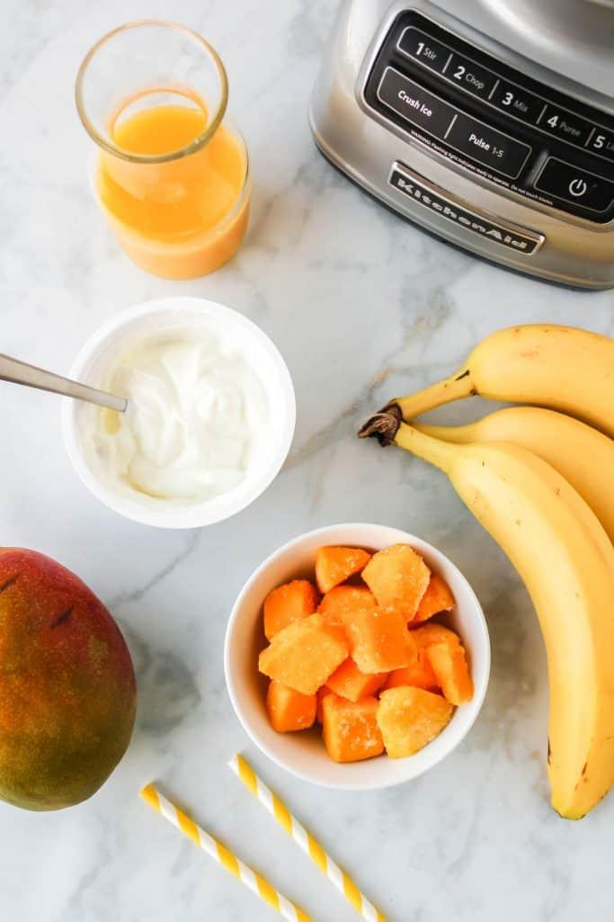 Ingredients needed for mango smoothies shown: orange juice, vanilla greek yogurt, frozen mango chunks and frozen banana.