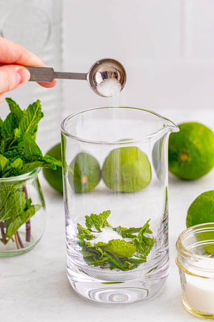 Glass container with mint leaves and sugar being poured in.