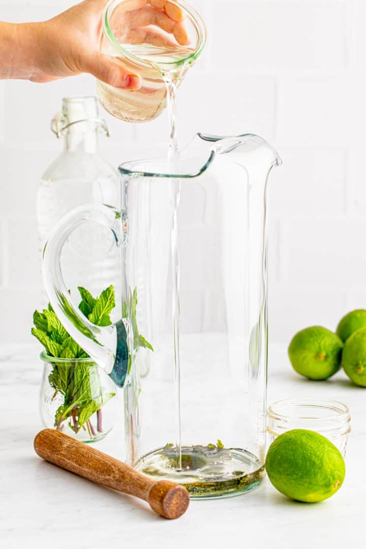 Simple syrup being cured into a tall glass pitcher.
