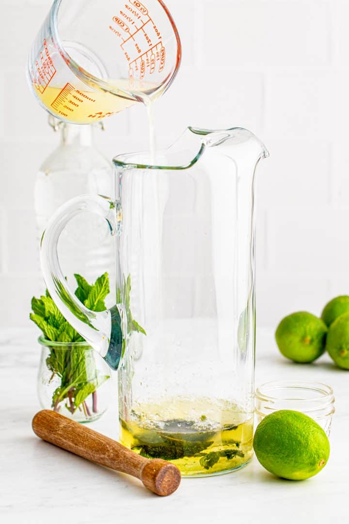 Lime juice being poured into a pitcher.