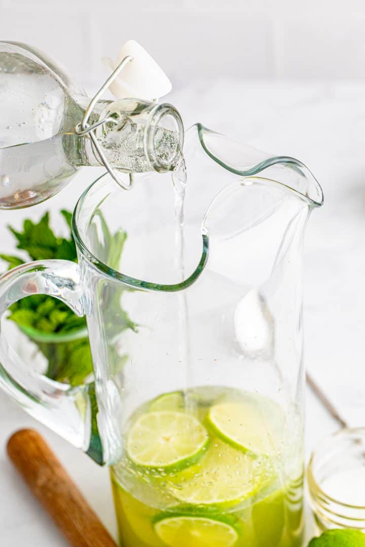 Club soda being poured into pitcher.