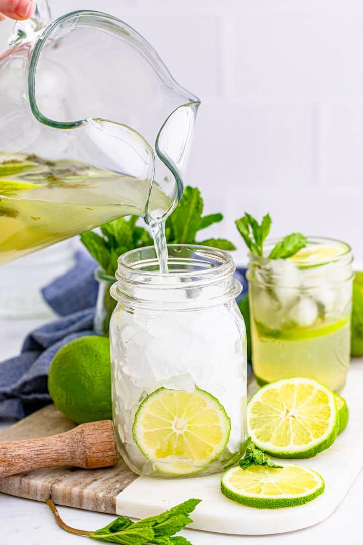 Pitcher pouring Summer Mojito Recipe into mason jar that is filled with ice.