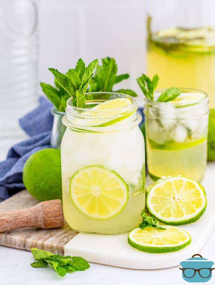 Summer Mojito Recipe in glass with pitcher with mint and lime garnishes.