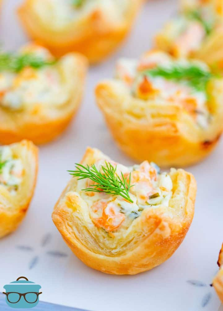Close up of Smoked Salmon Puff Pasty Bites topped with dill on platter