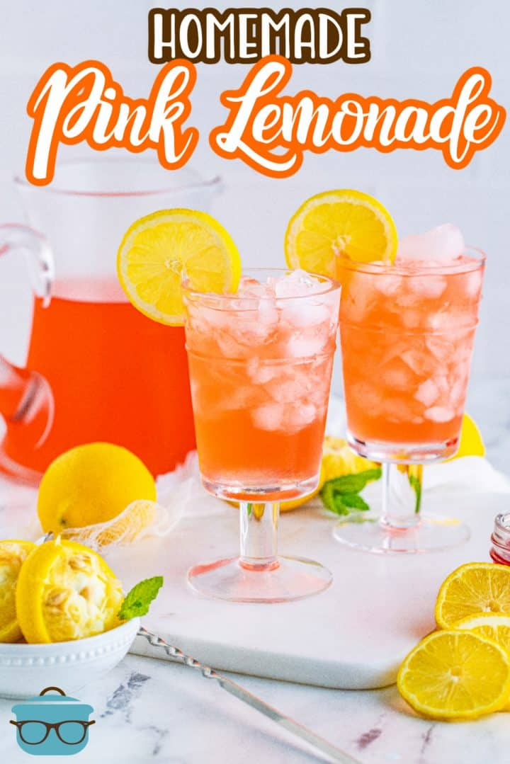 Two glasses of Homemade Pink Lemonade on white platter garnished with lemon with pitcher in background