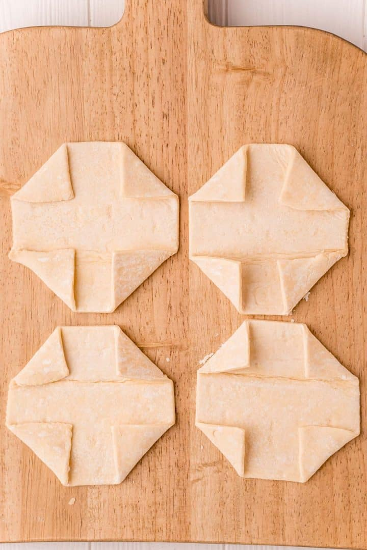 Puff pastry squares with edges folded in on wooden cutting board