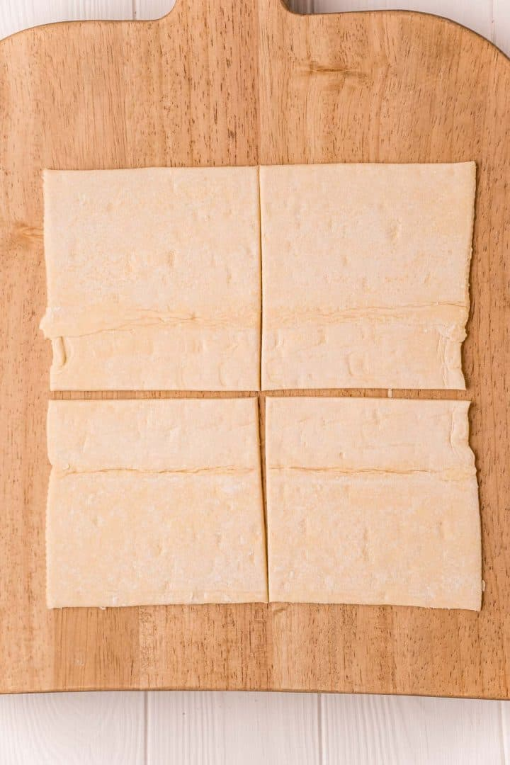 One sheet of puff pastry cut into 4 squares on wooden cutting board