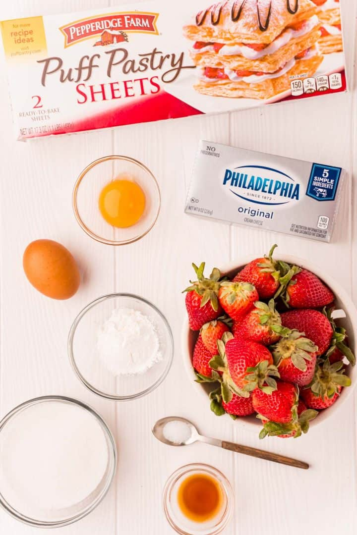 Ingredients needed: strawberries, cornstarch, granulated sugar, puff pastry, cream cheese, egg yolk, vanilla extract, salt, egg, water and powdered sugar