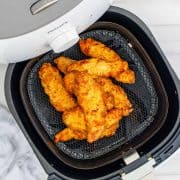 Square image overhead of finished Chicken Crispers in air fryer basket