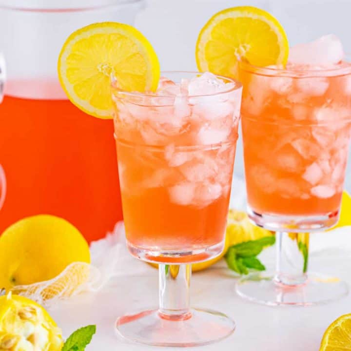 Square image of two glasses of Homemade Pink Lemonade garnished with lemon