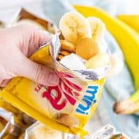 Square photo of hand holding bag of Walking Banana pudding showing bananas and vanilla wafers