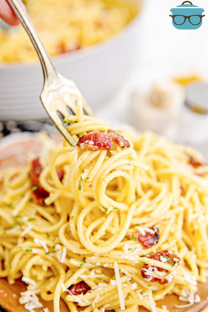 Fork holding up some Bacon Spaghetti Carbonara over a plate.