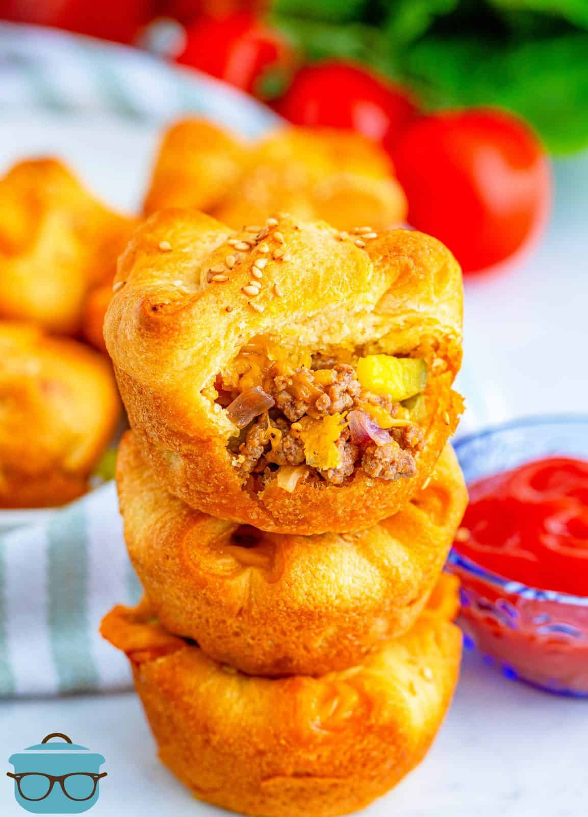 Three stacked Easy Cheeseburger Crescent Cups with top cup having a bite out of it.