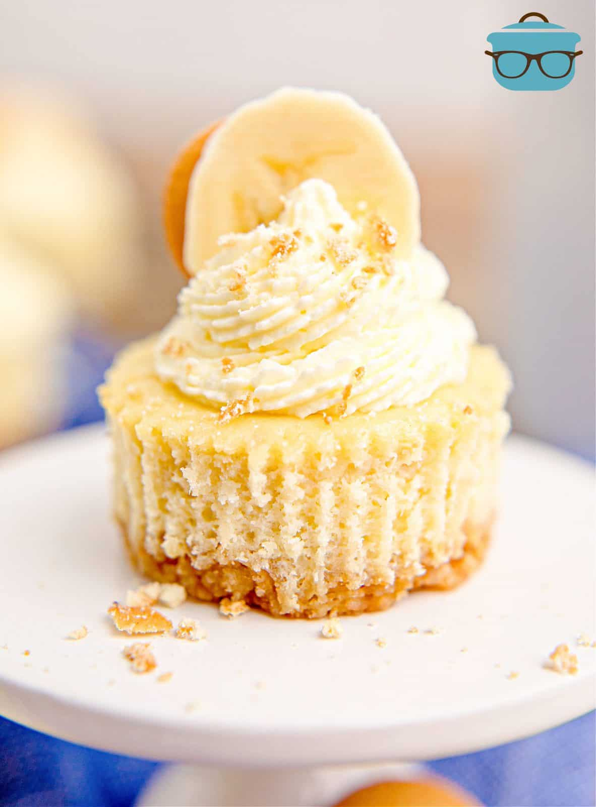 One Mini Banana Pudding Cheesecake on cupcake stand with whipped topping on top and a sliced banana.
