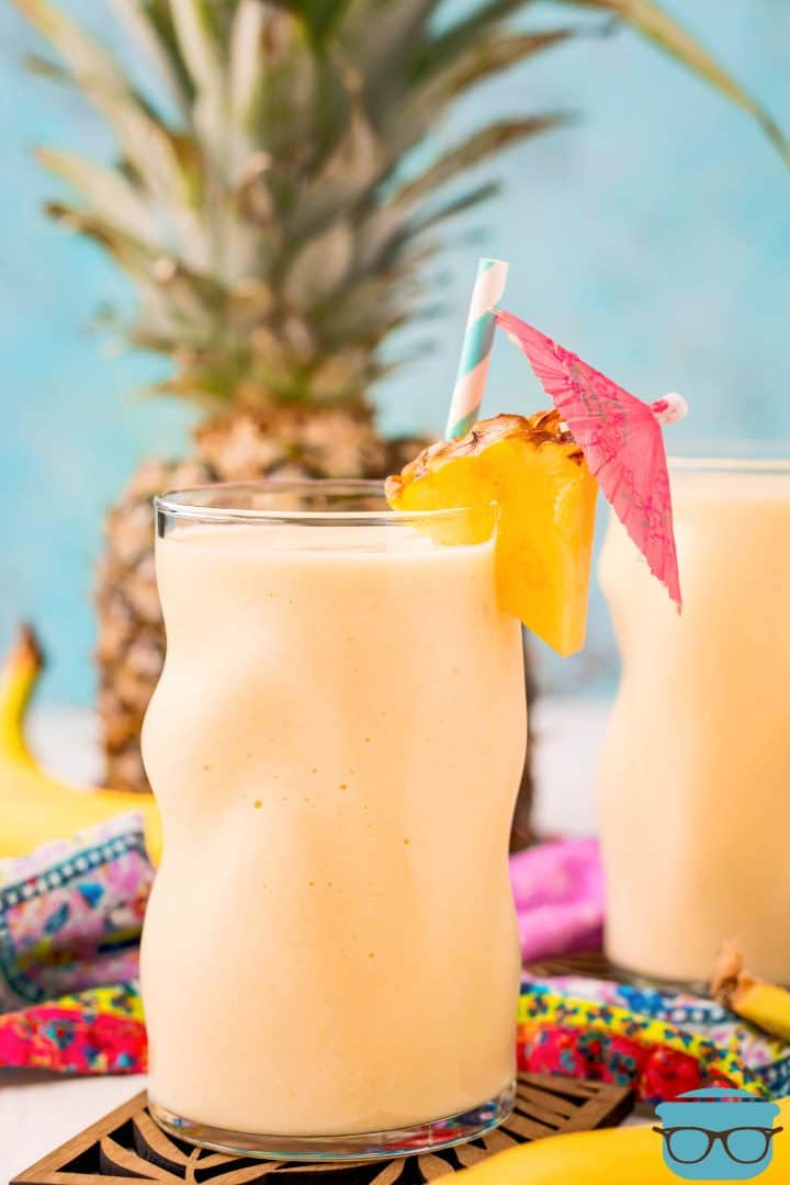 The Best Pineapple Smoothie in glass with pineapple slice, straw and drink umbrella.