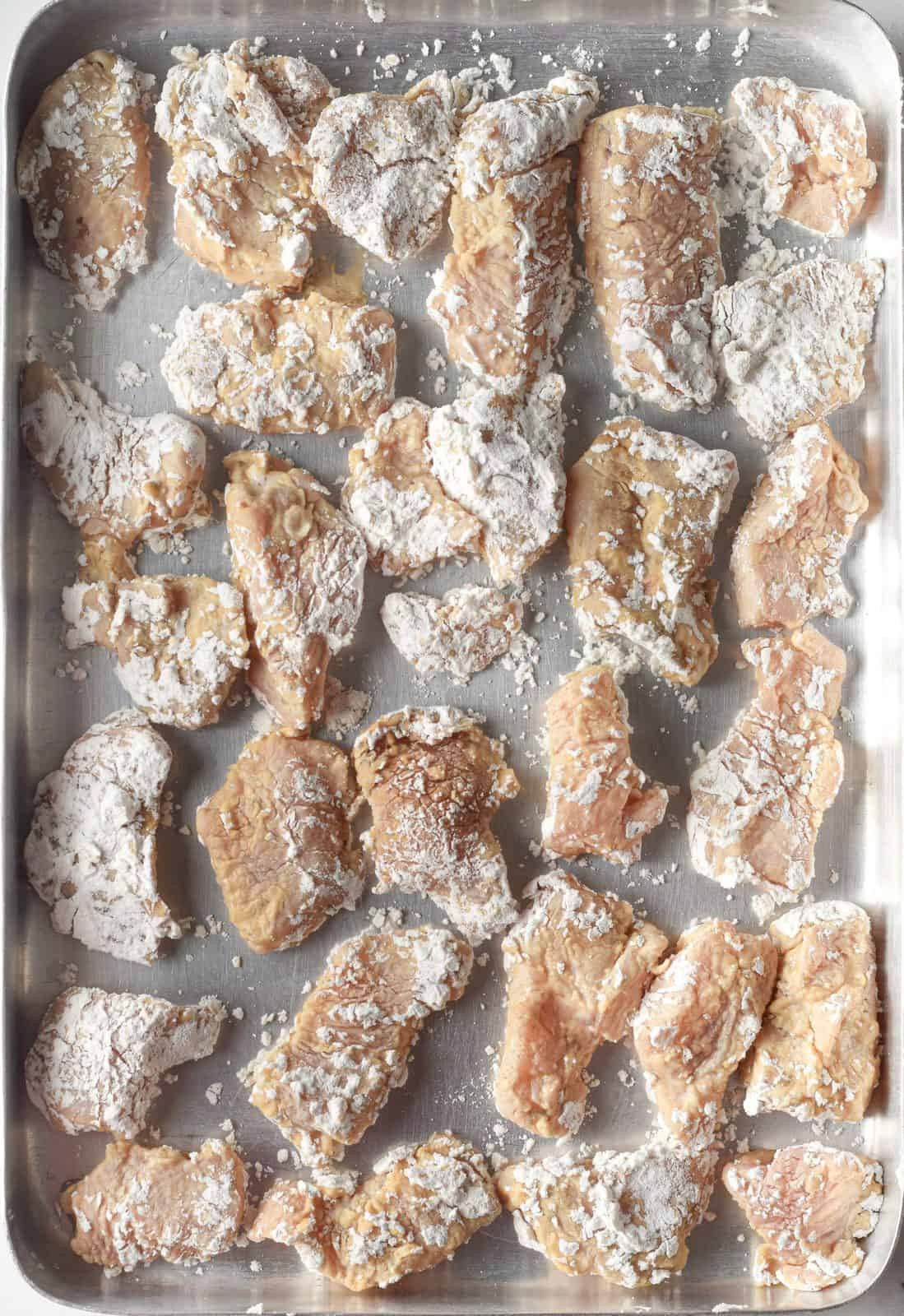 cornstarch coated chicken pieces laying in a single layer on a baking sheet.