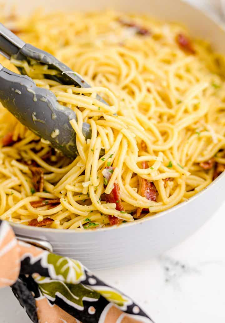 Tongs combining bacon into spaghetti mixture in skillet.