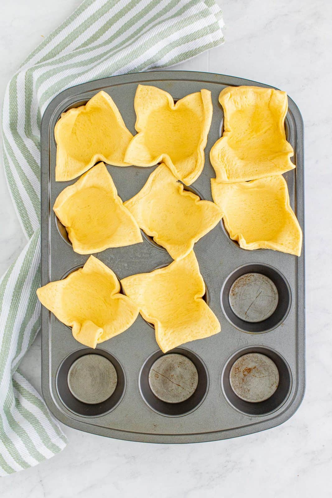 Crescent dough cut into squares and pressed into muffin tin.