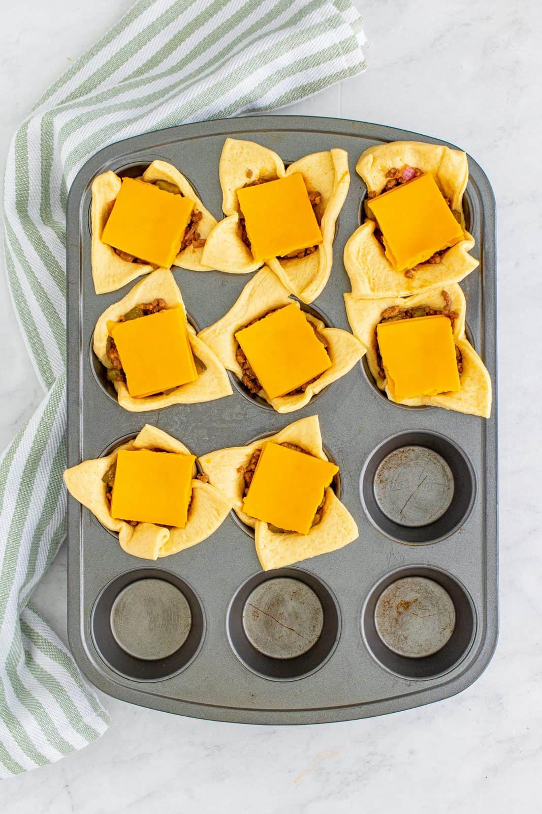 Cheese added to top of ground beef mixture in muffin tin.