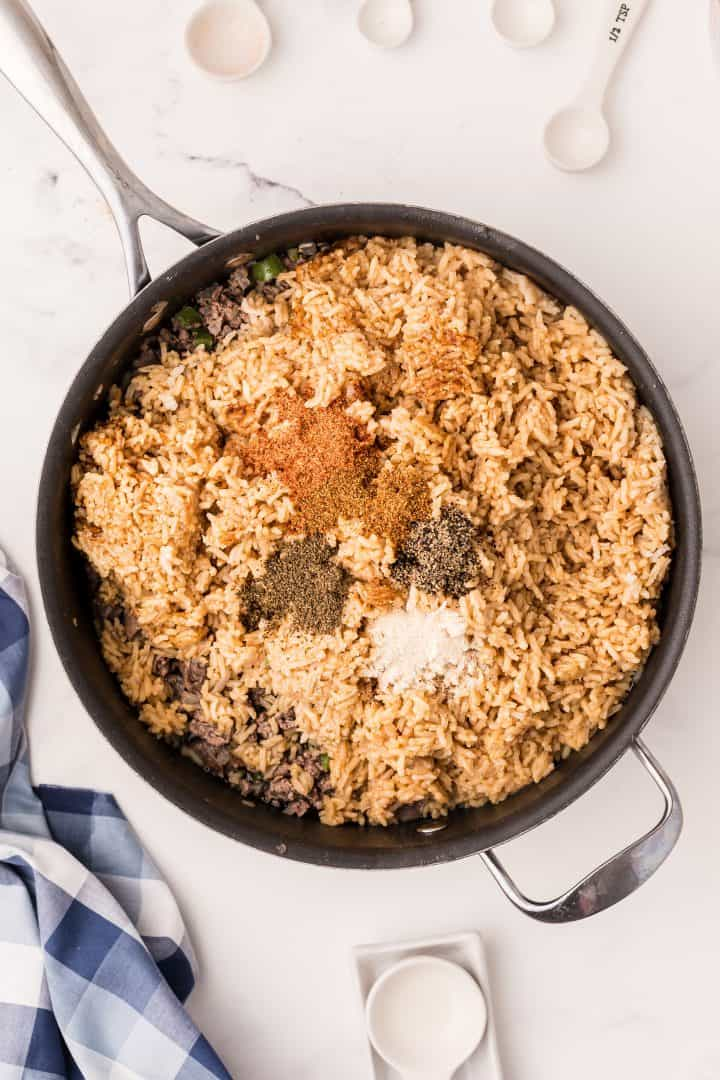Rice, celery seed, creole seasoning, cayenne pepper, onion powder, cayenne pepper and water added to skillet.