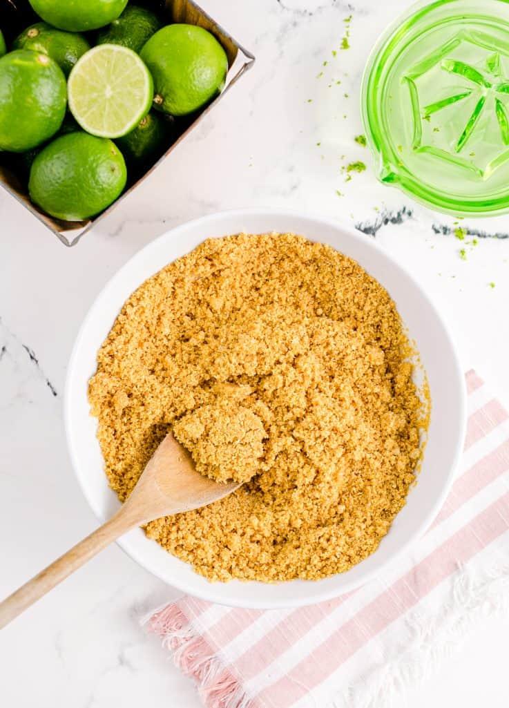 Spoon stirring up the graham cracker mixture