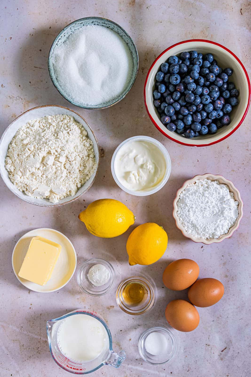 Ingredients needed to make bundt cake: all-purpose flour, baking powder, salt, blueberries, unsalted butter, granulated sugar, vanilla extract, eggs, buttermilk, sour cream, lemon juice, lemon zest and powdered sugar.