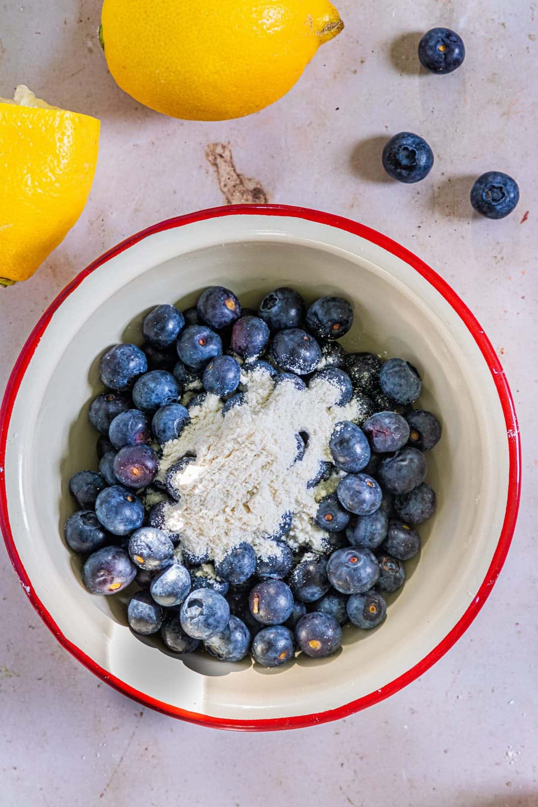 Flour added to blueberries in a white bowl.