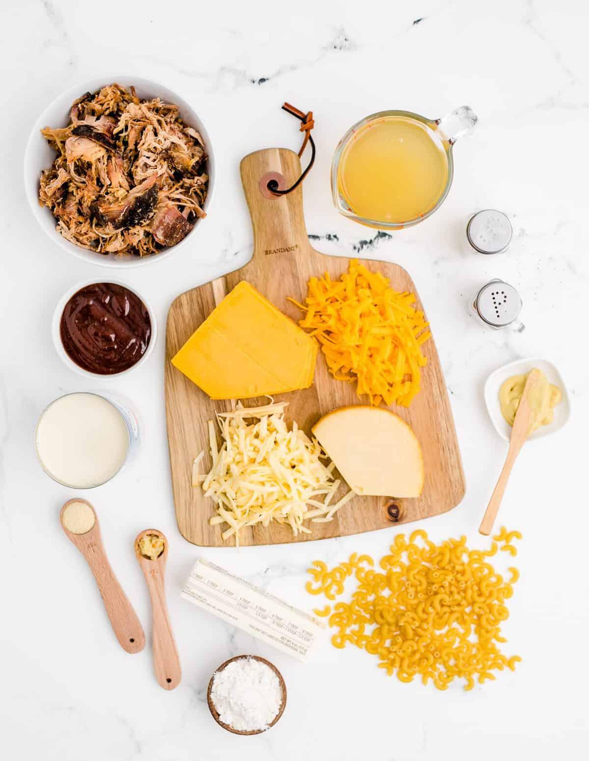 Ingredients needed: macaroni, salted butter, all-purpose flour, evaporated milk, chicken broth, salt, pepper, dijon mustard, onion powder, garlic, cheddar cheese, gouda cheese, pulled pork and BBQ sauce.