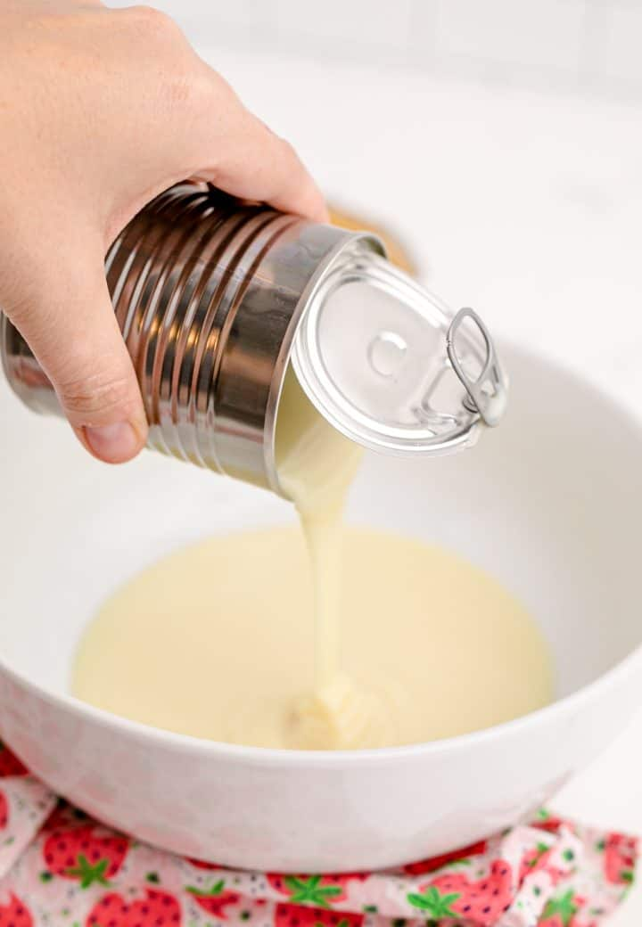 Sweetened condensed milk being poured into a bowl.