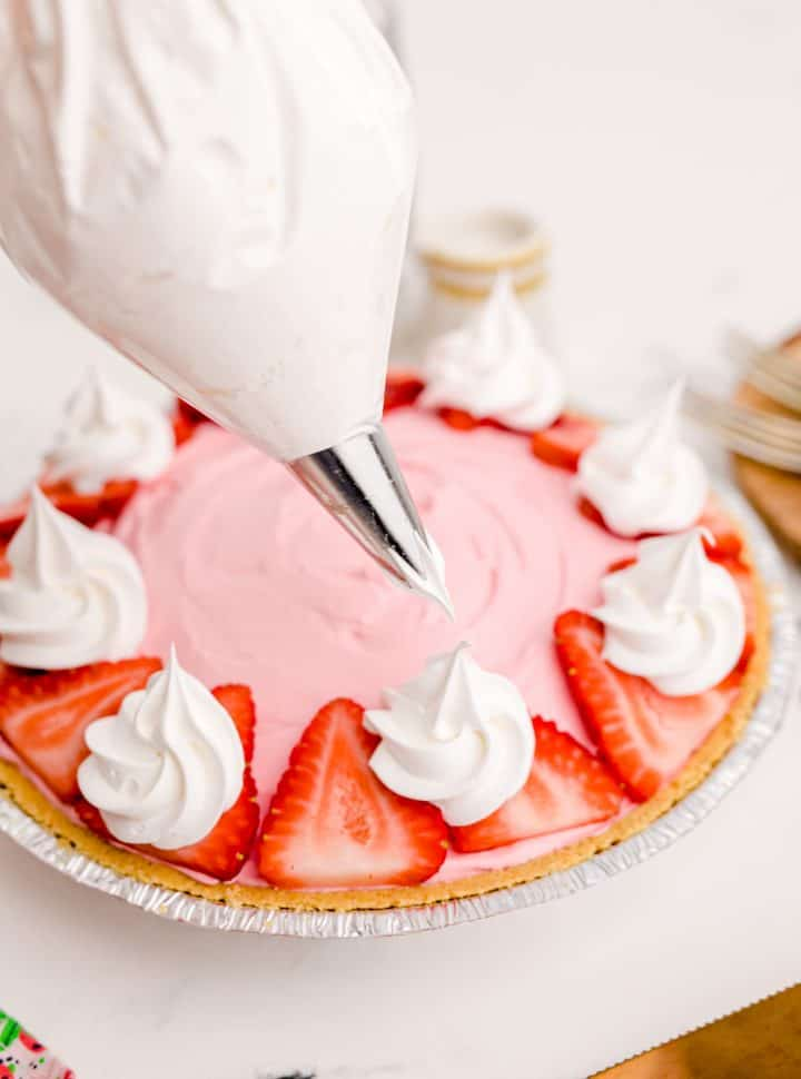 Strawberry Kool-Aid Pie Recipe being garnished with strawberries and cool whip. A piping bag is being held over the pie.