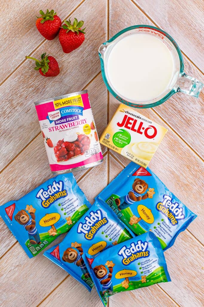 Ingredients needed: instant cheesecake pudding, milk, honey teddy grahams, strawberry pie filling and sliced strawberries
