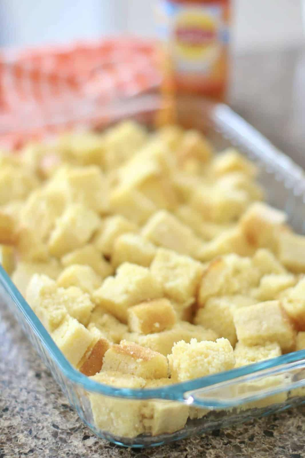 cubed pieces of cornbread shown layered in the bottom of a glass baking dish.