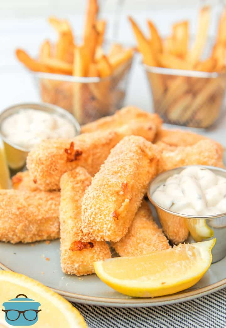 Air Fryer Homemade Fish Sticks stacked with dipping sauce and sliced lemon