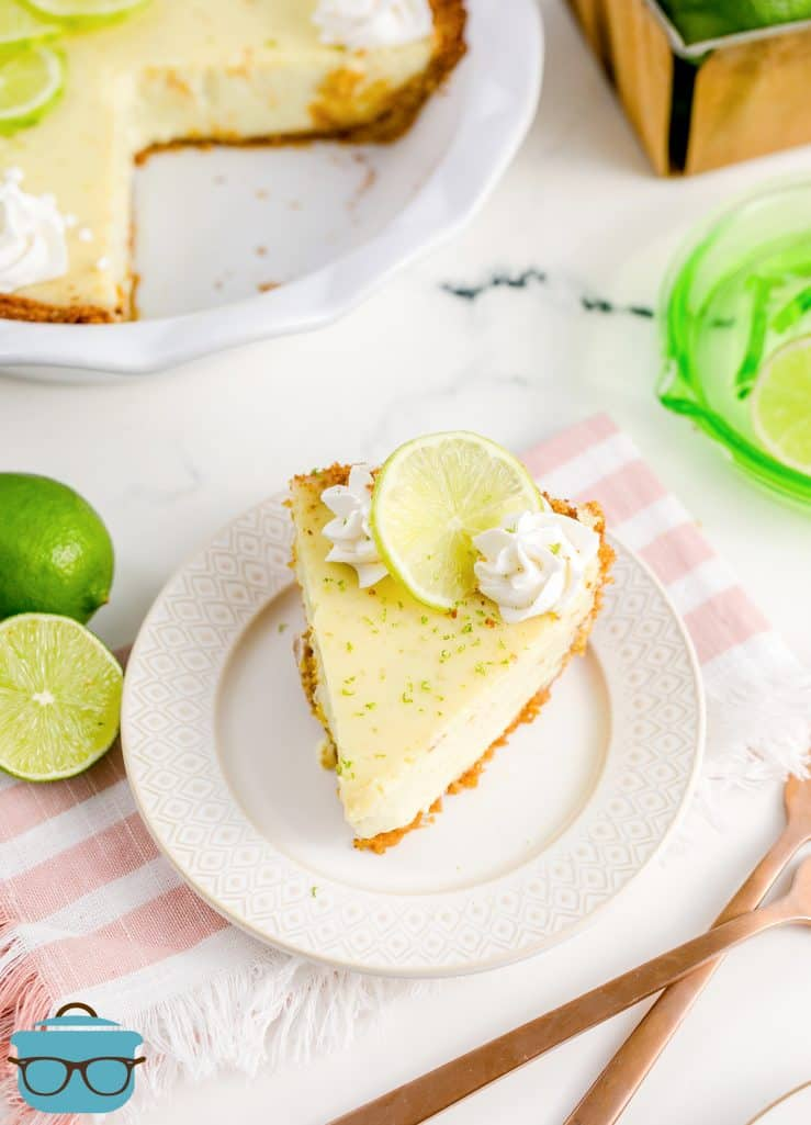 Slice of Key Lime Pie on white plate with whole pie in background