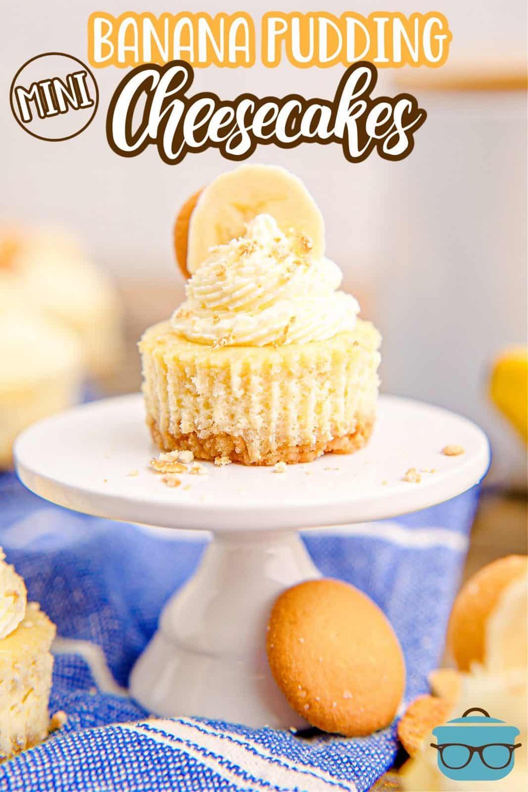 Pinterest image of decorated Mini Banana Pudding Cheesecake on white stand with cheesecakes behind it.