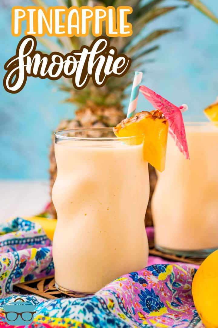 Two Pineapple Smoothies in glasses garnish with pineapple slices, straws and drink umbrellas.