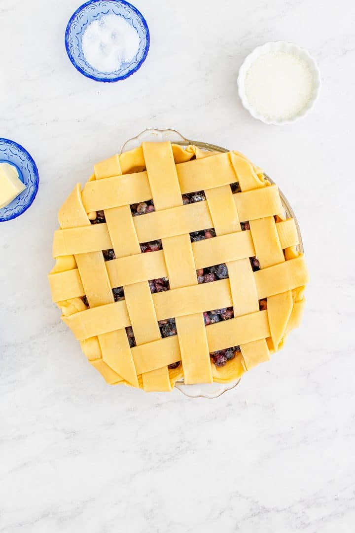 Finished lattice pie crust on top of blueberry pie.