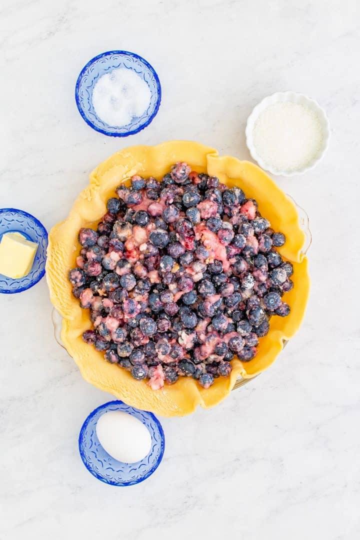 Blueberry Pie filling in bottom crust in pie pan.