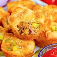 Close up of stacked Easy Cheeseburger Crescent Cups with top cup having bite out of it